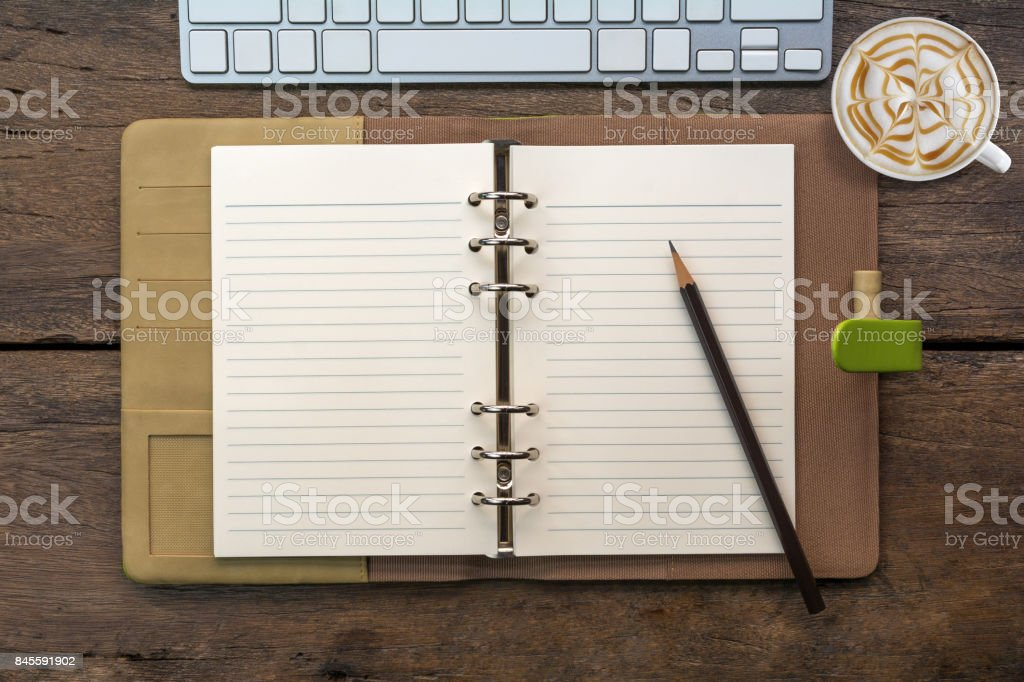 Blank notebook open page with pencil, keyboard and cup of cappuccino coffee stock photo