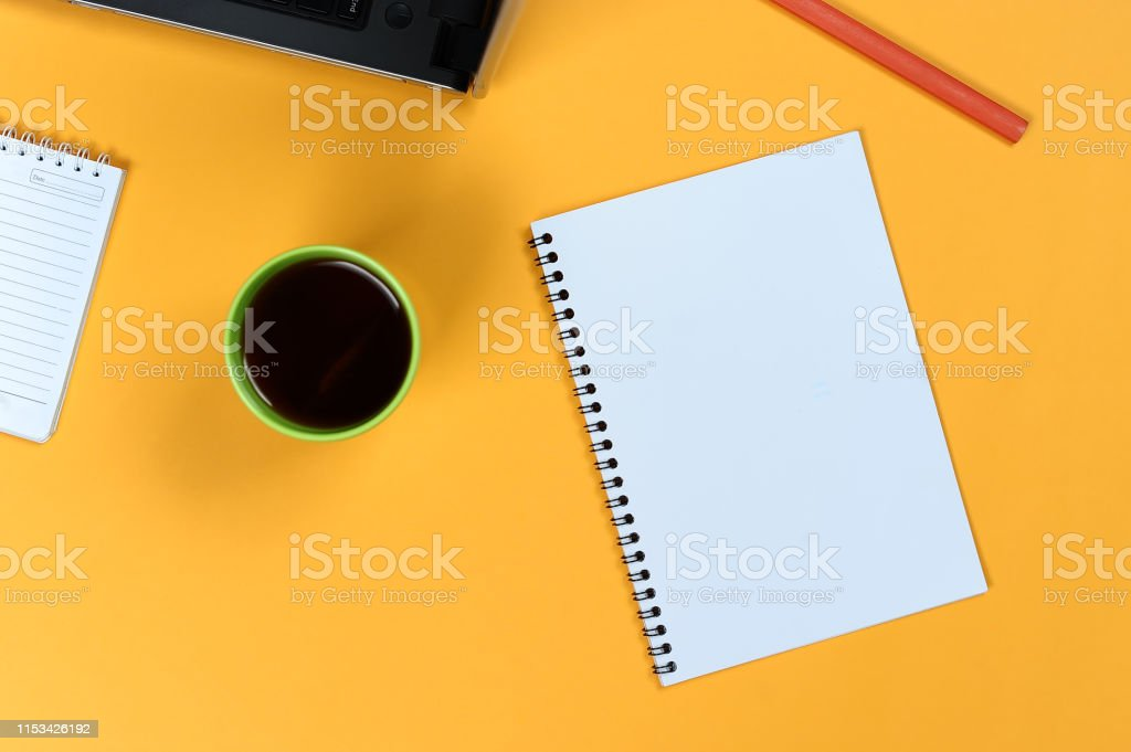 Blank notebook page, laptop, coffee cup and pencil. Blank writing pad...