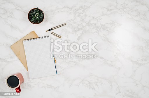 istock Blank notebook page on white marble table background 643894730