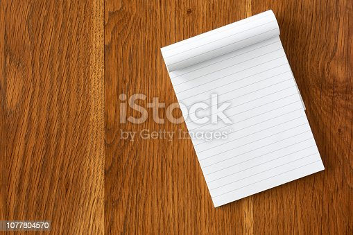 Top view of blank open notebook page with lines on dark wooden background with copy space. For use as mock up