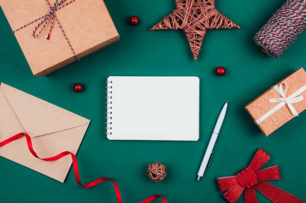 Leere Notizbuch, Stift, Handwerk Geschenk-Boxen, Umschlag, roter Bogen, Band und Dekorationen über grünen festlichen Hintergrund. Neujahrsplanung. – Foto
