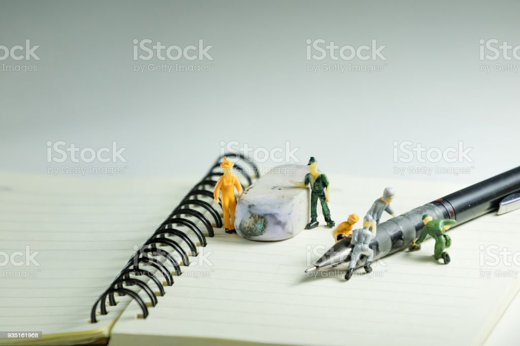 Blank notebook, pencil and eraser with miniature models stock photo
