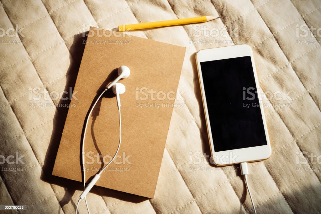 Blank notebook with cellphone on canvas stock photo