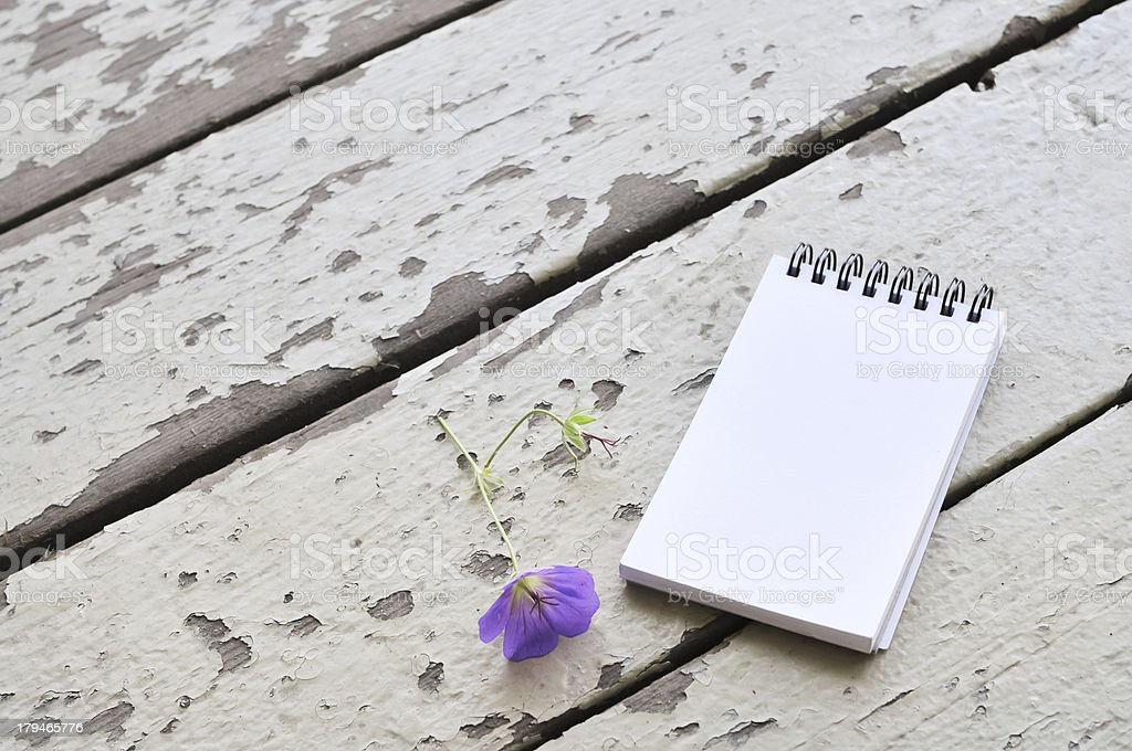 blank notepad and violet flower on rustic plank wood background royalty-free stock photo