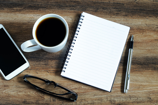Blank notepad, eye glasses, coffee, pen and smart phone
