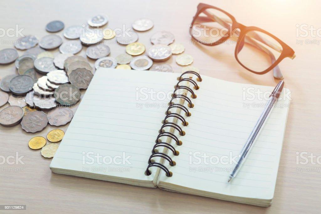 Boş not defteri, kalem, gözlük ve hafif bir arka plan üzerinde paralar. - Royalty-free Ahşap Stok görsel