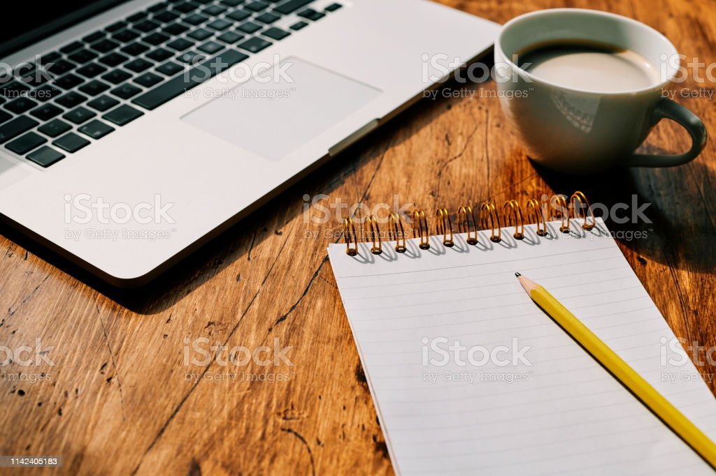 Blank notepad, pencil, coffee, Laptop, Work desk background. stock photo