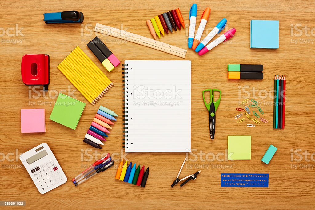 Blank notepad surrounded by school supplies on wooden table stock photo