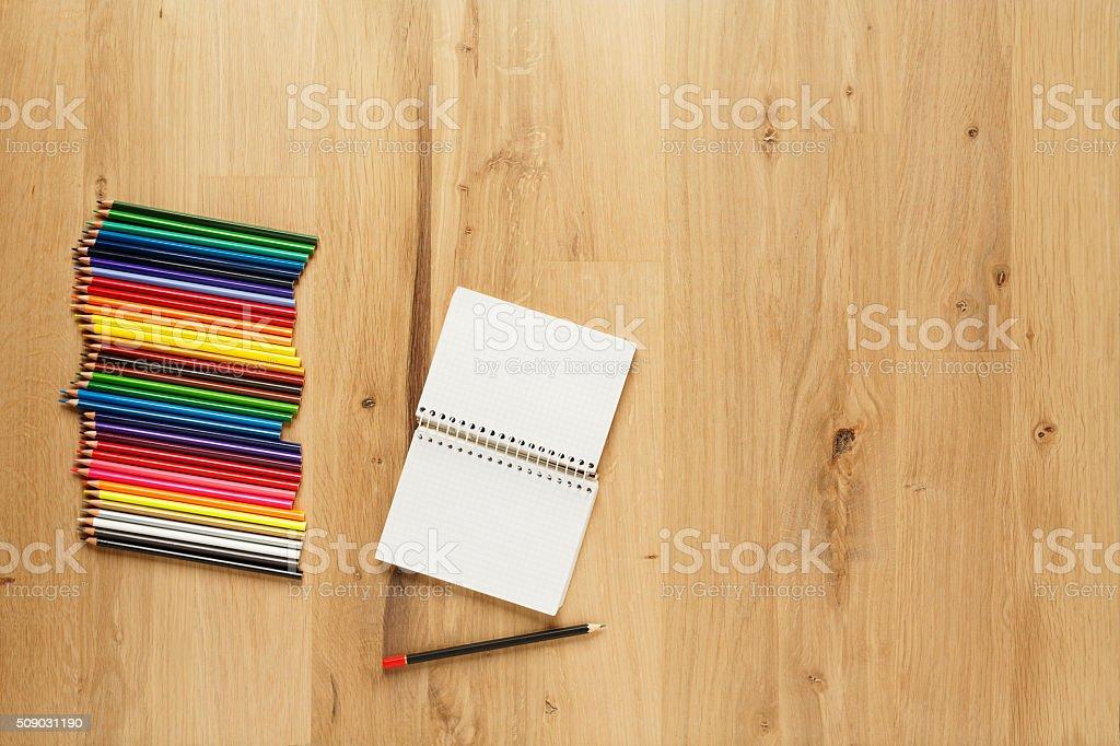 Holzfußboden Parkett ~ Leeren notizblock mit buntstifte auf holzfußboden parkett