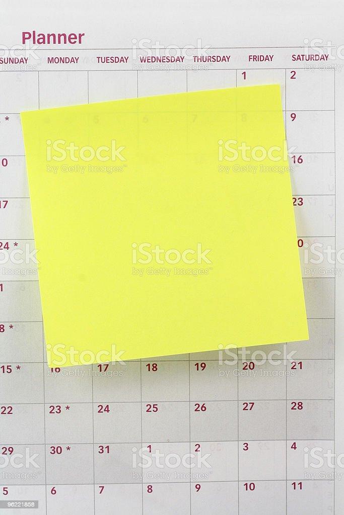 blank notepaper sticking on calendar royalty-free stock photo