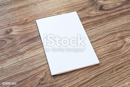 istock Blank of brochure is on a wooden desk. 529081402