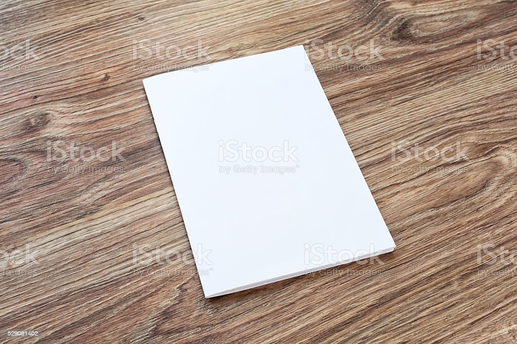 Blank of brochure is on a wooden desk. stock photo