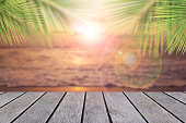 Blank of Top table wood on blurry sea sunlight and palm leaf for add product of advertisement.