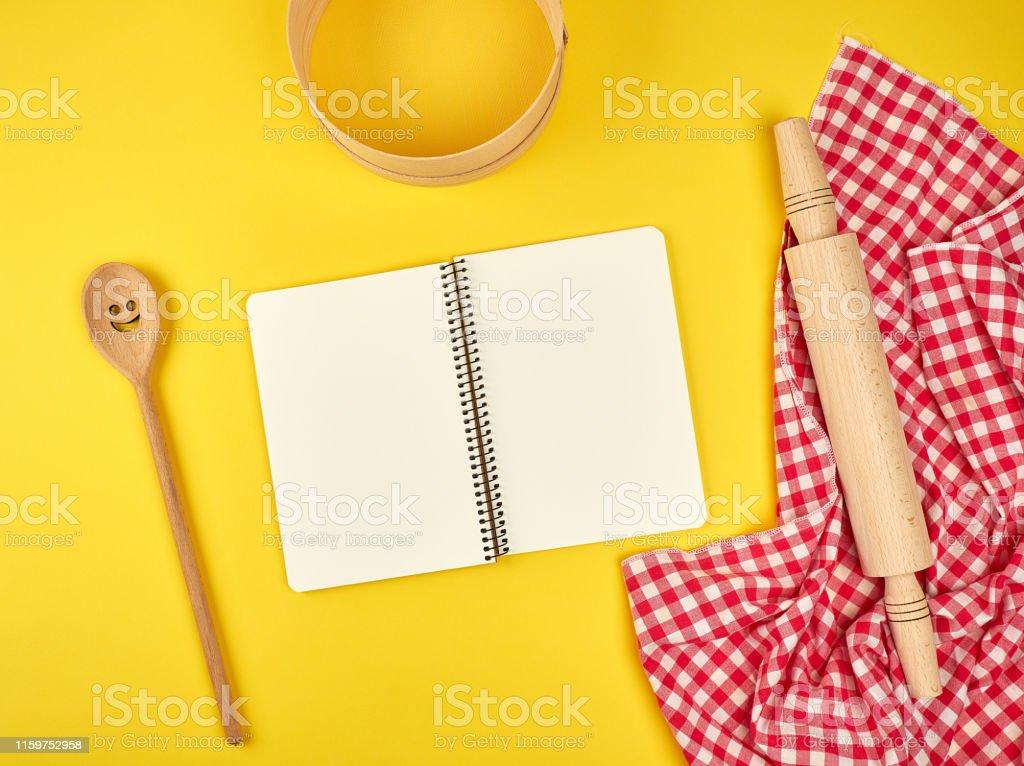blank open notebook and wooden kitchen accessories, round sieve,...