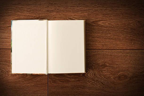 Blank open notebook on a dark wooden surface stock photo