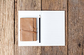 Blank open notebook with black pencil on wood table
