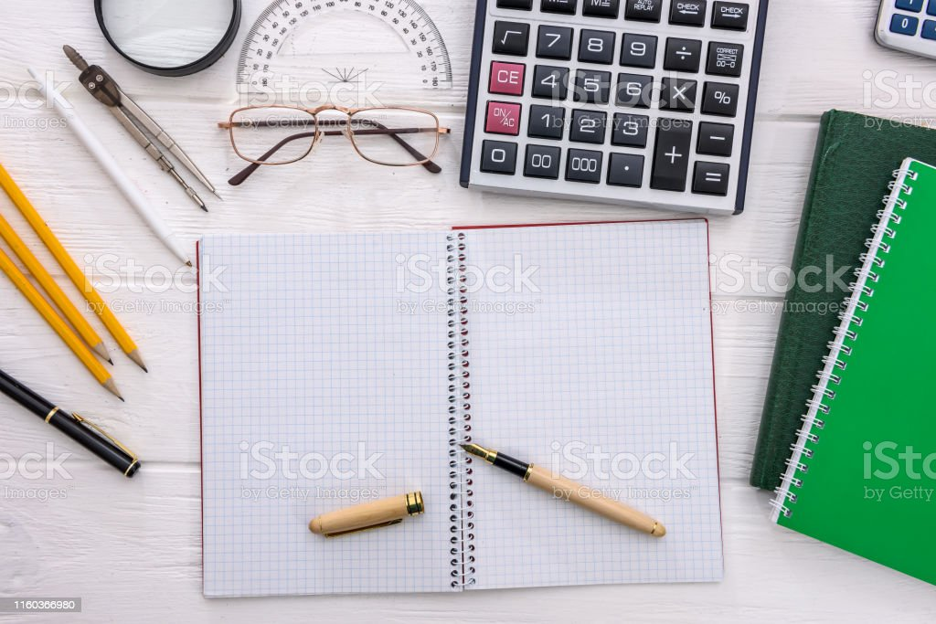 Blank open notepad on table with studying tools