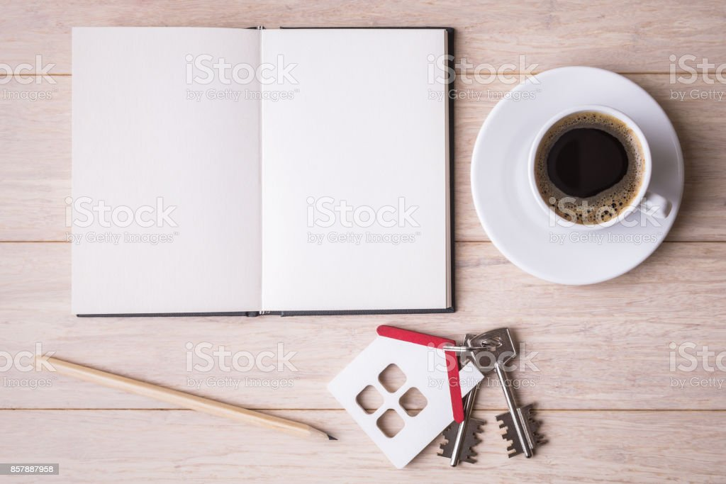 Blank open sketchbook, coffe cup and house model with keys stock photo