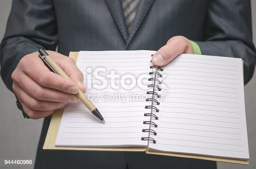 Businessman holds in hand a note pad with pen. To do list template. Goals or business tricks. Business tips concept. Task Manager