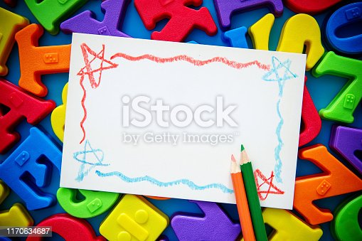istock Blank Painting paper on multi colored alphabets background 1170634687