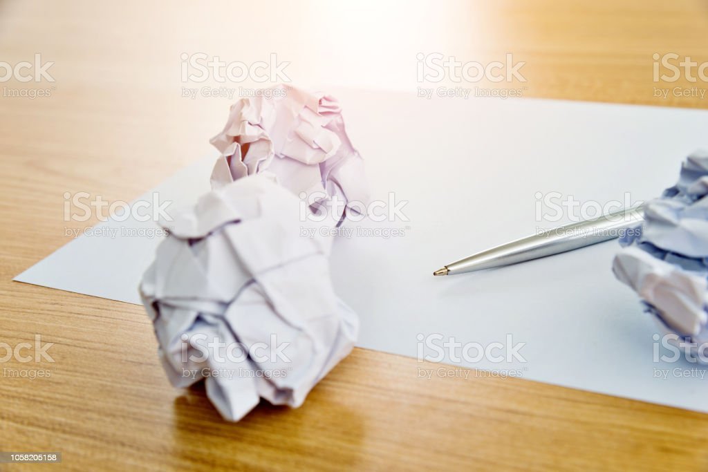 Blank paper and crumpled paper balls on wooden table.