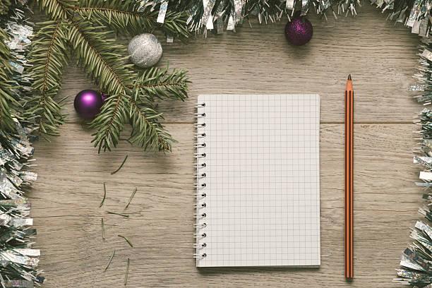 blank paper and pen framed with christmas decorations - weihnachts wunschliste stock-fotos und bilder