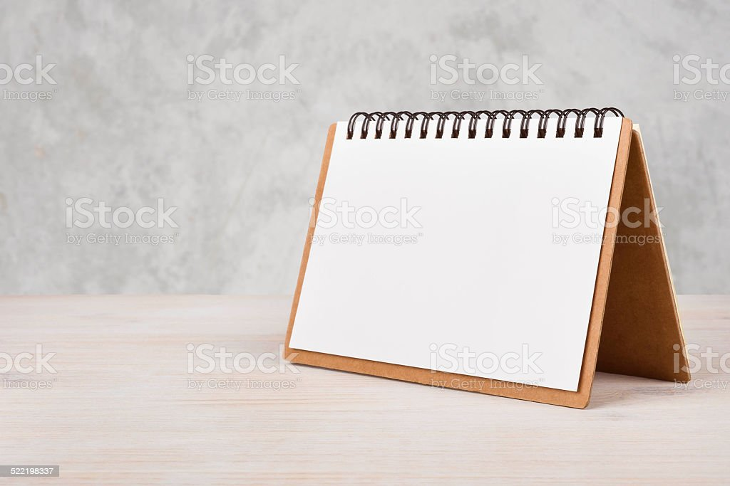 Blank paper calendar on wooden table stock photo