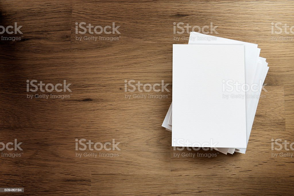 Blank paper card on wooden table stock photo