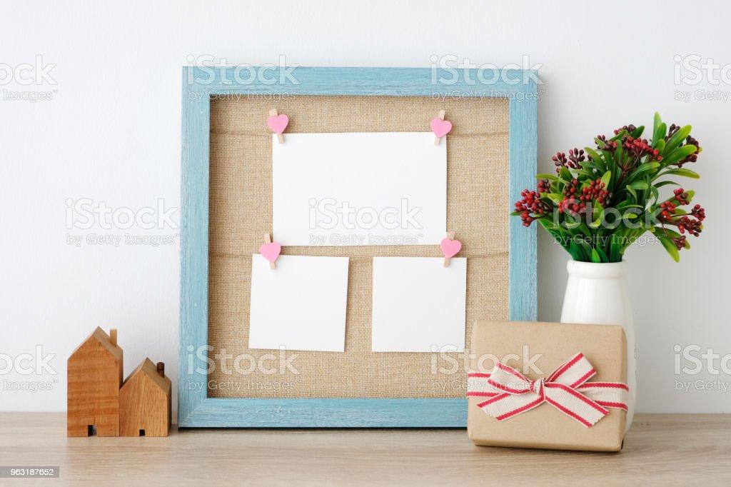 Cartões de papel em branco pendurado na azul vintage frame de madeira e caixa de presente no fundo da tabela, cópia espaço para texto, aniversário, feliz aniversário e convite cartão - foto de acervo