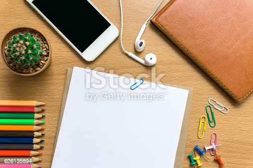 blank paper,  color pencil, and smart phone on wood desk / can you write text message / copy space / top view