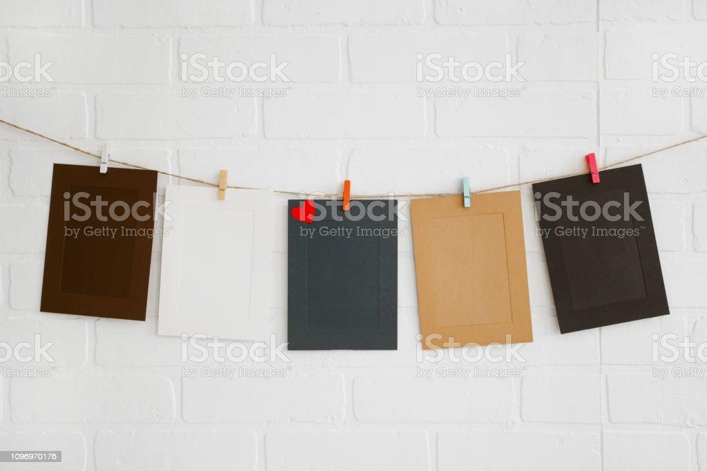 Quadros de papel em branco na parede de tijolo branco - foto de acervo