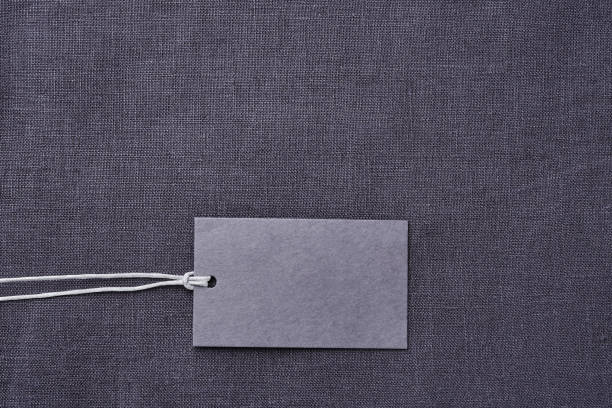 Blank paper label on gray linen clothes background stock photo