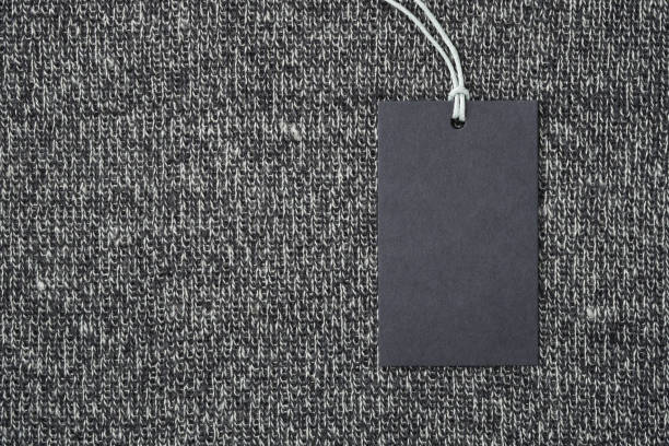 Blank paper label on knitted wool clothes background stock photo