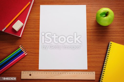 Blank paper and school supplies on desk.