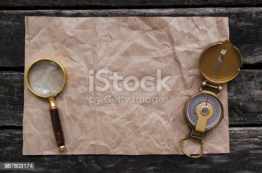 Blank crumpled paper page with copy space for treasure map for example, compass and magnifying glass.  Seaching, discovering, revealing and exploring concept background.