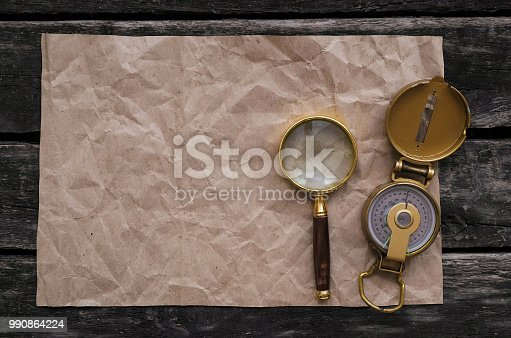 Blank crumpled page with copy space for treasure map, compass and magnifying glass on old adventure table background.