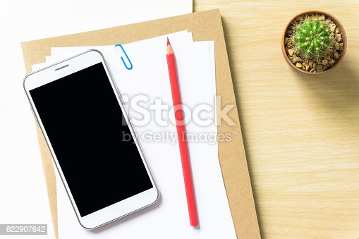 621843818istockphoto blank paper, pencil, and smart phone on wood desk 622907642