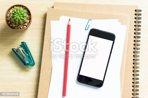 621843818istockphoto blank paper, pencil, and smart phone on wood desk 623909426