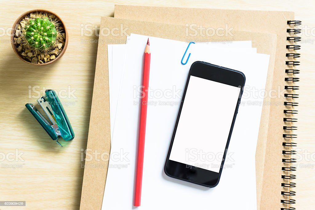 blank paper, pencil, and smart phone on wood desk stock photo