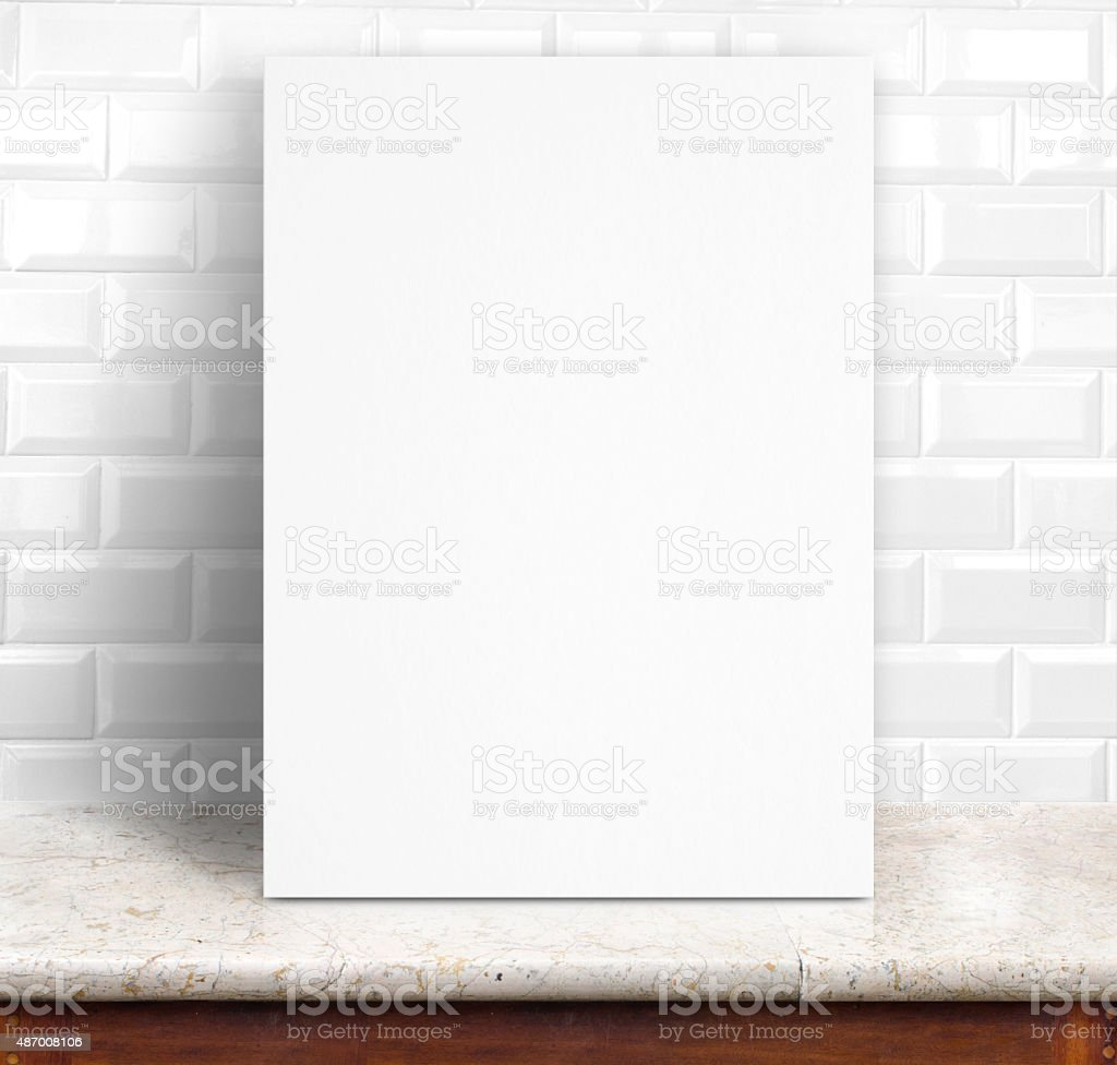 Blank paper poster lean at tiles wall and marble table stock photo