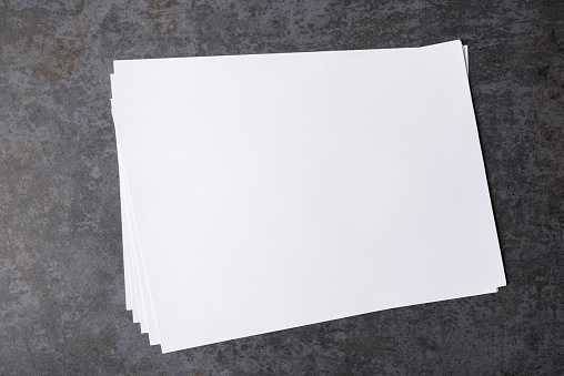 Blank Paper Sheet On Dark Stone Background Stock Photo - Download Image Now
