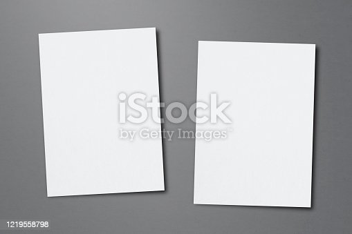 932100364 istock photo Blank paper sheets for brochure on grey background, top view. Mock up 1219558798