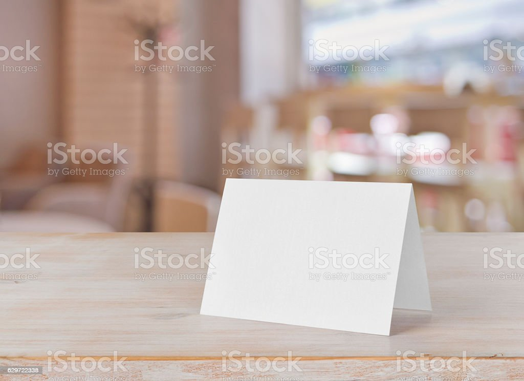 Blank paper table card on wooden table over bar background stock photo