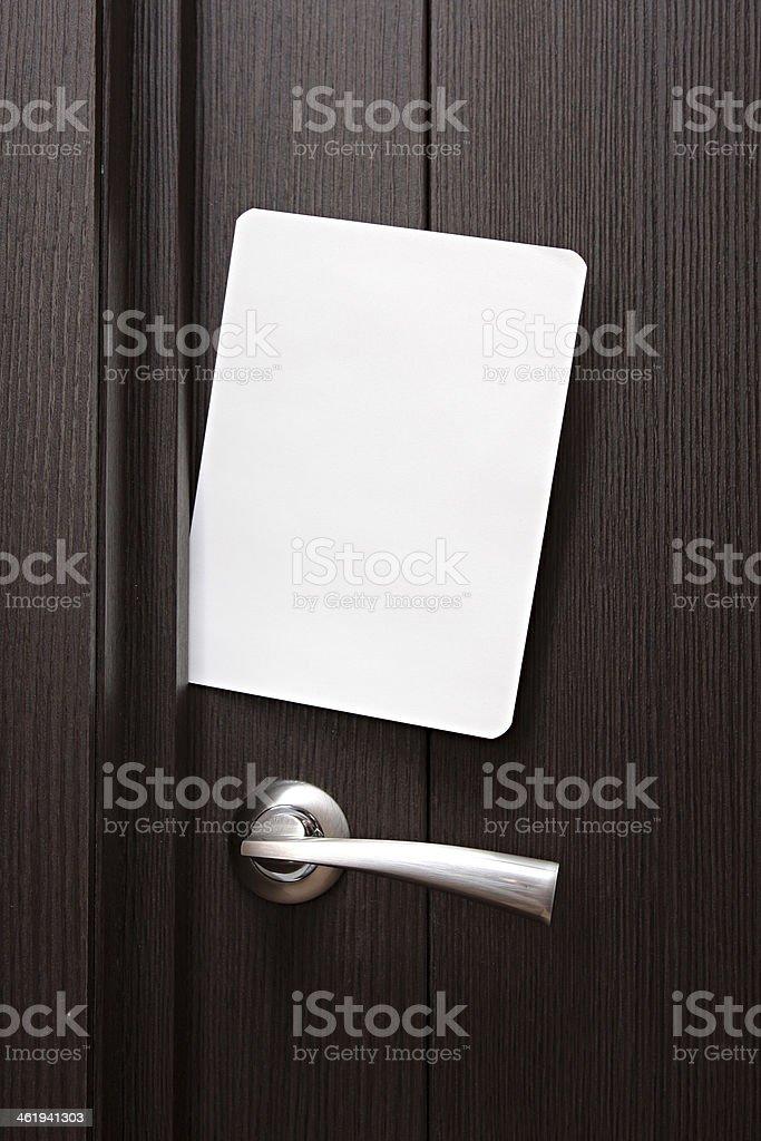 Blank paper to write  nested in gap under wooden door. stock photo