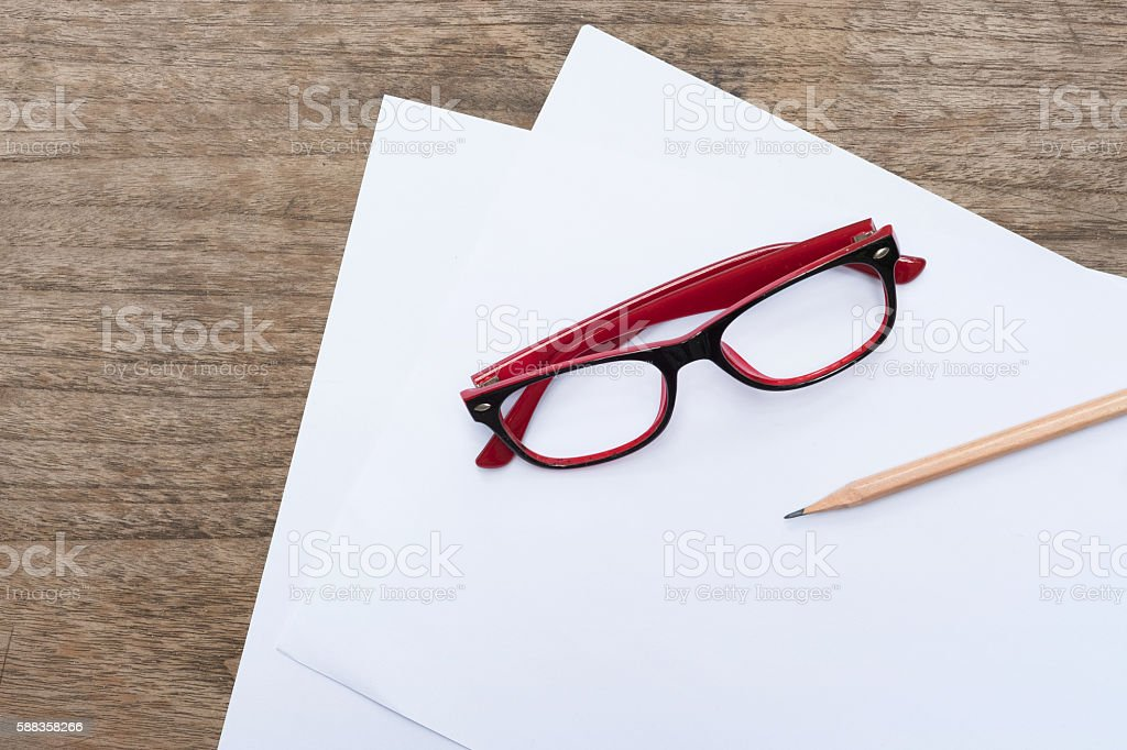 Blank paper with pencil and eye glasses on wood table. stock photo