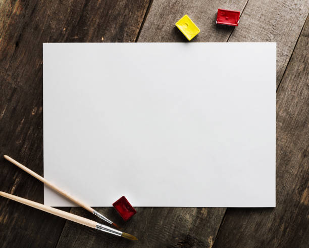 Blank paper with watercolor and brushes on the wooden table for mockups