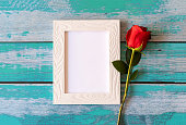 istock Blank photo frame and red roses over wooden table 1248674890