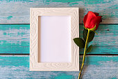 istock Blank photo frame and red roses over wooden table 1248674891