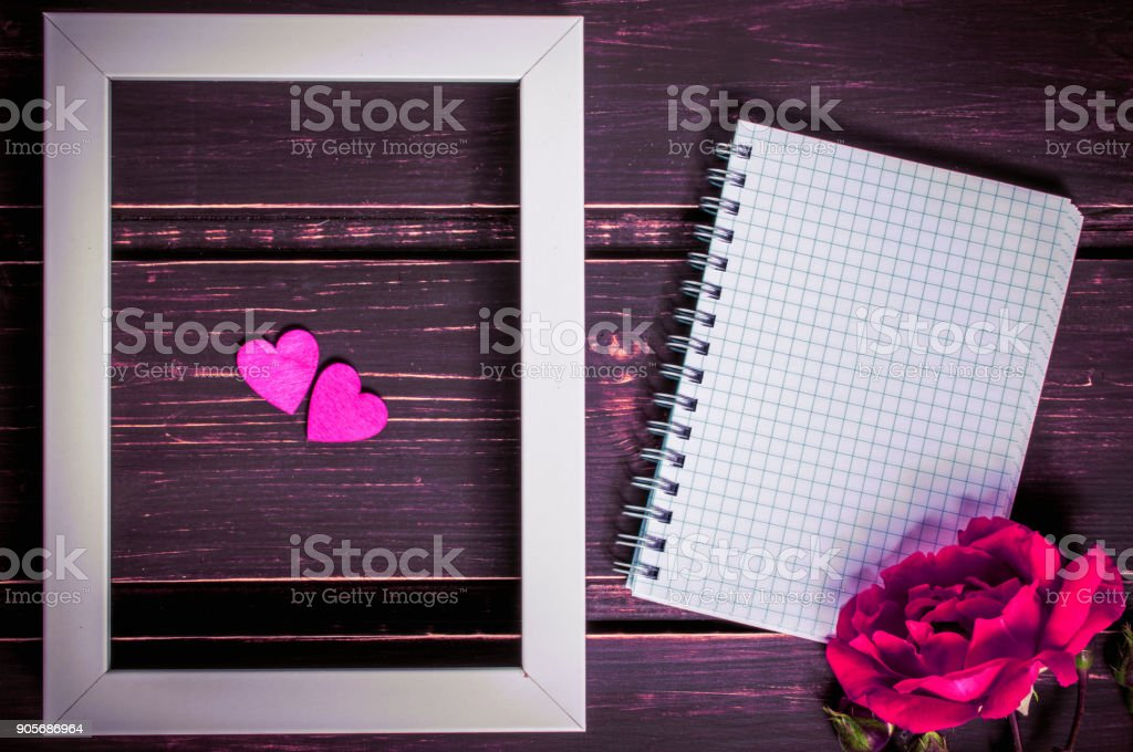 blank photo frame with two hearts , blank notebook with copyspace and pink rose flowers on wooden background. greeting card and holiday concept. stock photo