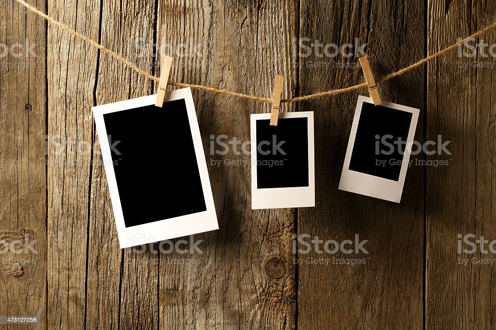 Blank photographs hanging on old wooden wall stock photo